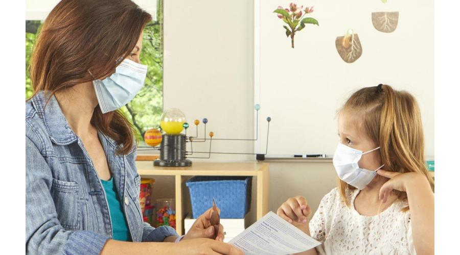teacher and child wearing PPE masks