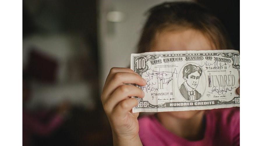 girl holding up 100 dollar bill