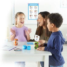 two students and a teacher making silly faces playing with their learn about feelings activity set