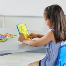 kindergarten girl tracing her finger along the star breathing pattern on her mindful mazes board