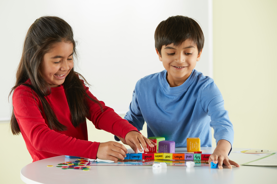 A young boy and a young girl play together with a hands-on social-emotional learning product at a small table.