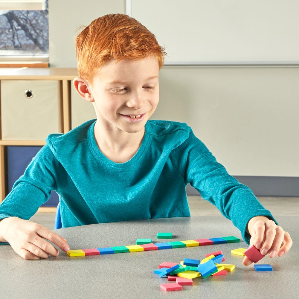 red head boy in a green shirt working with color tiles