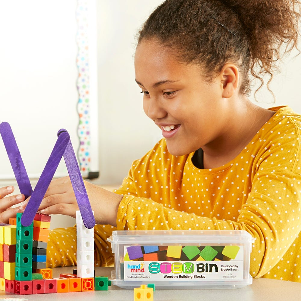 Girl in a yellow shirt building with STEM bins