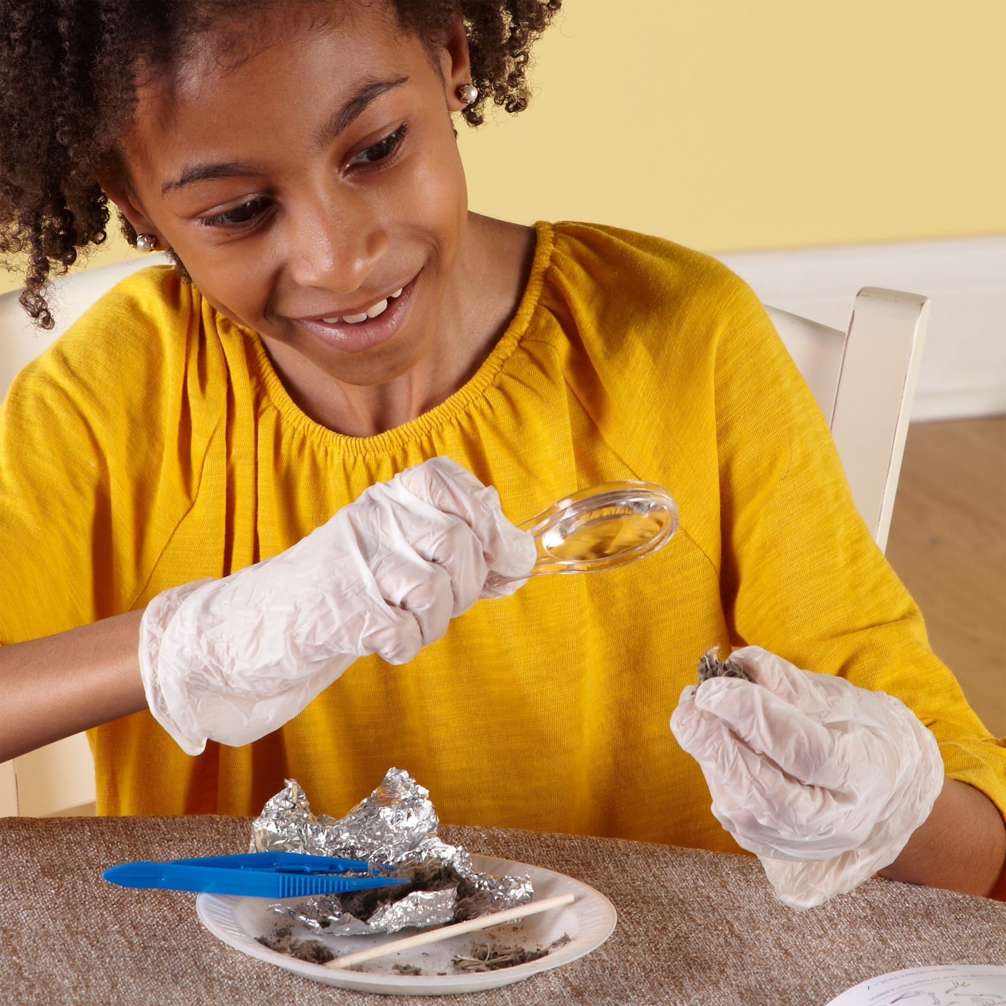 Girl in a yellow shirt looking at bones in an owl pellet