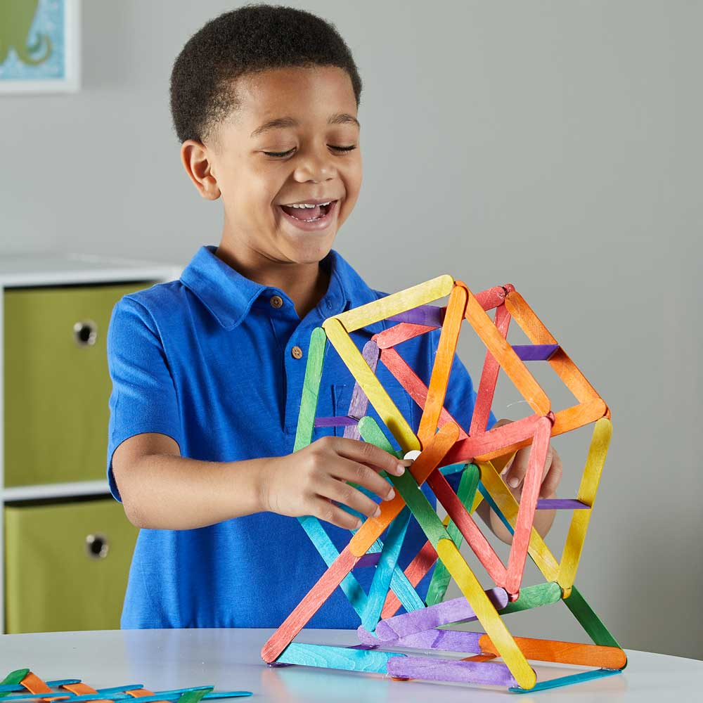 Boy in a blue shirt playing with a craft stick creations wheel