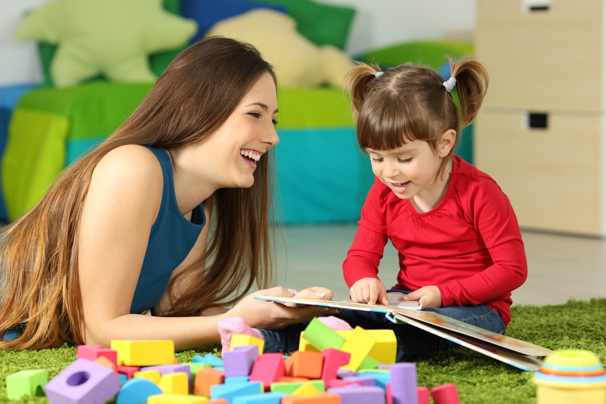 Girl and a woman on a green carpet reading a book with building blocks around them