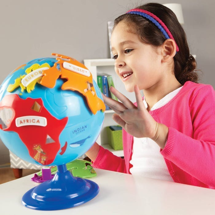girl in a pink sweater playing with a puzzle globe