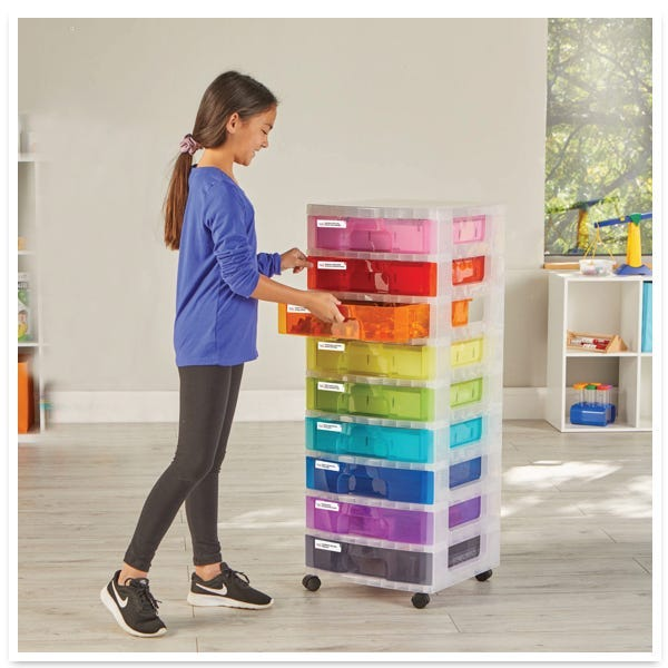 girl standing with the classroom makerspace cart opening the drawers