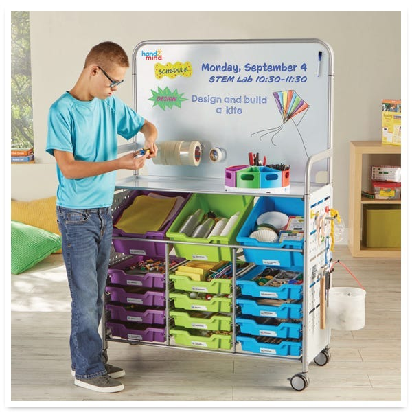 boy student standing in front of the Makerspace Lab cart