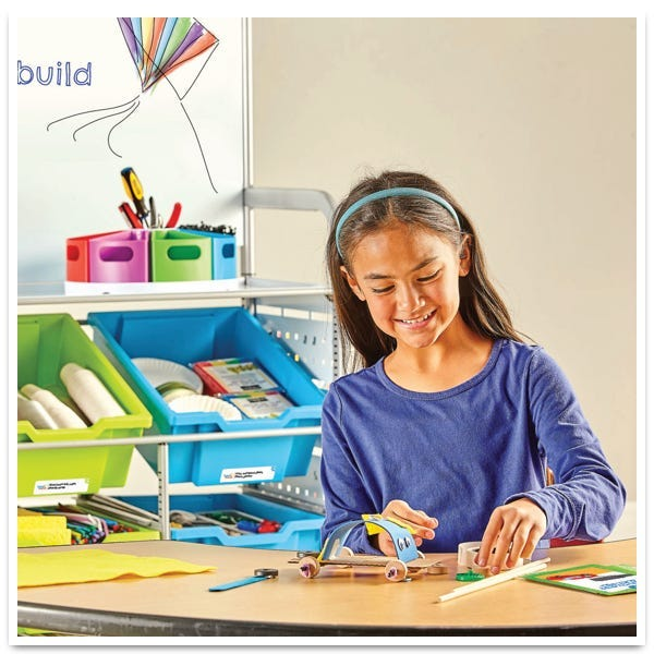 girl in a blue shirt making a creation with the makerspace lab kit