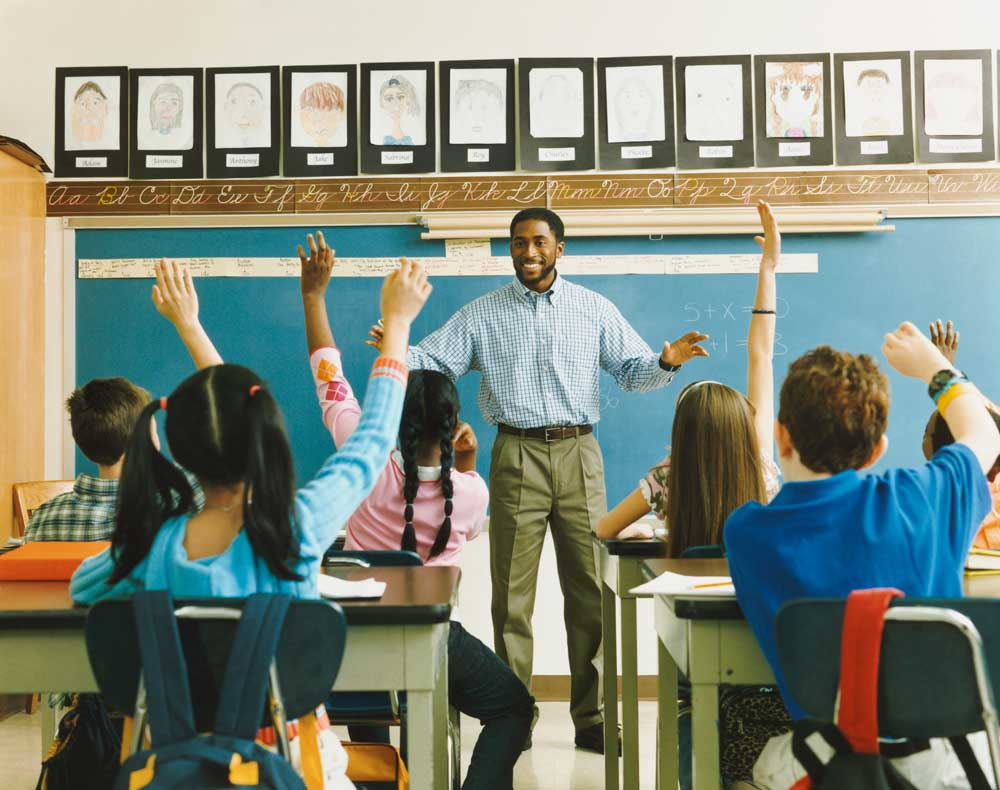 Teacher standing in front of a group of students raising their hand