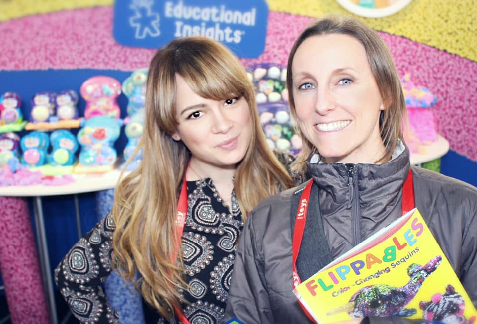 2 employees in front of the play foam display at New York Toy Fair
