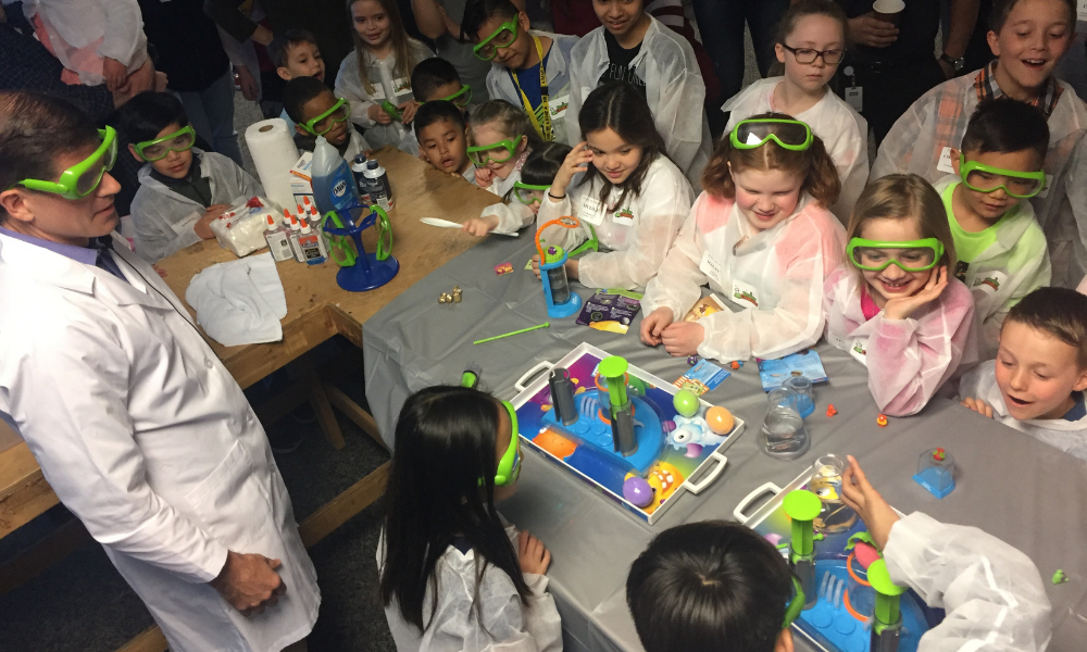 a group of kids using beaker creatures at our take your child to work day