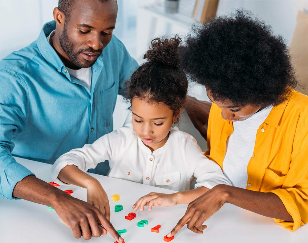 dad and mom working with a child with counters for family engagement