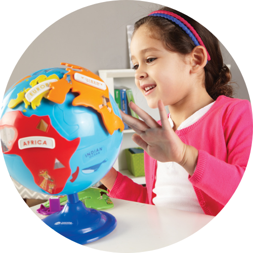 girl in a pink cardigan looking at the puzzle globe