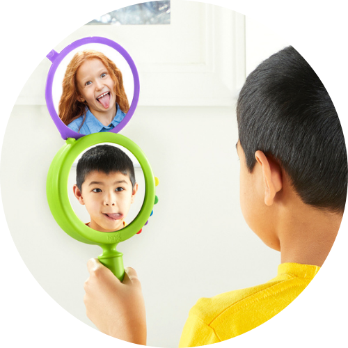boy in a yellow shirt holding up a see my fillings mirror showing the silly face.