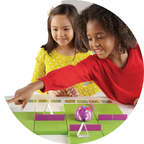 a girl in a yellow shirt and a boy in a red shirt playing with the coding mouse activity set