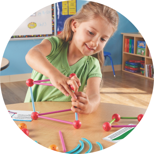 girl in a green shirt building a model with a stem set