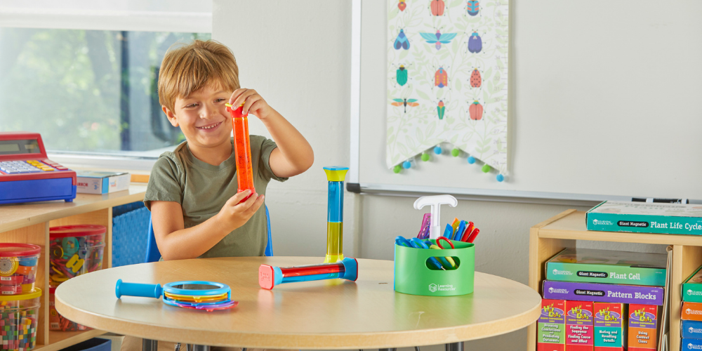 Little boy sitting at a table in a classroom, playing with Color-Mix Sensory Tubes
