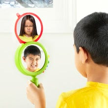 boy in yellow shirt looking in his see my feelings mirror making an angry face like the girl in the demonstration picture