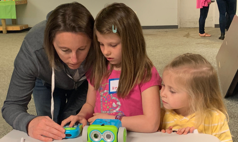 a mom and 2 little girls learning how to code on botley the robot